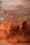 Poudre de cacao en baisse sur une table en bois Photo stock
