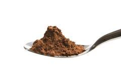 Poudre de cacao sur la cuillère Photo stock