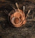 Poudre de chocolat dans le plat de metall avec des cuillères sur le fond en bois foncé Photographie stock libre de droits