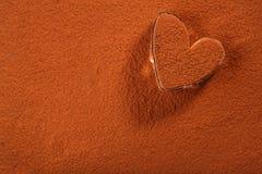 Poudre de chocolat de cacao avec le verre en forme de coeur épousseté image libre de droits