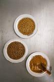 Poudre de coriandre avec des graines noires et blanches Photo stock