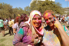 Poudre de couleur sur le festival de printemps de sourire de deux dames Images libres de droits