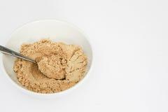 Poudre de gingembre dans la cuvette blanche avec la cuillère en métal, d'isolement sur le blanc Photos stock