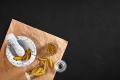 Poudre de Haldi de safran des indes dans la petite cuvette avec entier cru en mortier de marbre au-dessus de fond noir avec l'esp Image stock