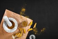 Poudre de Haldi de safran des indes dans la petite cuvette avec entier cru en mortier de marbre au-dessus de fond noir avec l'esp Photos stock