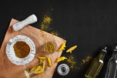 Poudre de Haldi de safran des indes dans la petite cuvette avec entier cru en mortier de marbre au-dessus de fond noir avec l'esp Photographie stock