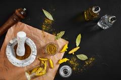 Poudre de Haldi de safran des indes dans la petite cuvette avec entier cru en mortier de marbre au-dessus de fond noir avec l'esp Photo stock
