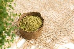 Poudre de henné pour le mehendi de teinture de cheveux et de sourcils et de dessin sur des mains, avec les feuilles vertes, les  photos stock
