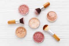 Poudre de maquillage avec des brosses sur le fond en bois photo stock