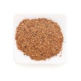 Poudre de noix de muscade dans une cuvette blanche sur le blanc Photographie stock libre de droits