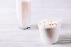 Poudre de protéine dans le scoop sur la table en bois blanche images libres de droits