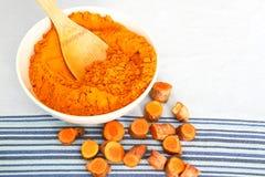 Poudre de safran des indes dans la cuvette avec des morceaux de racine de safran des indes Photographie stock libre de droits