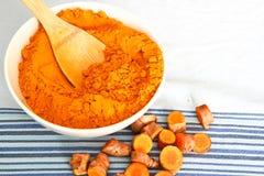 Poudre de safran des indes dans la cuvette avec des morceaux de racine de safran des indes Images libres de droits