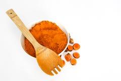 Poudre de safran des indes dans la cuvette avec des morceaux de racine de safran des indes Image stock