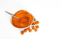 Poudre de safran des indes dans la cuvette avec des morceaux de racine de safran des indes Photo libre de droits