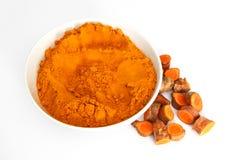 Poudre de safran des indes dans la cuvette avec des morceaux de racine de safran des indes Photo stock