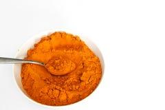 Poudre de safran des indes dans la cuvette avec la cuillère en métal d'isolement sur le blanc Image libre de droits
