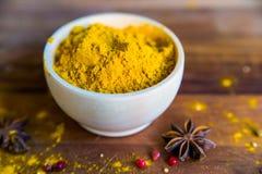 Poudre de safran des indes dans la cuvette sur la table en bois Images stock