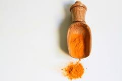 Poudre de safran des indes et scoop en bois sur le blanc Image stock