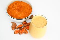 Poudre de smoothie de safran des indes et de safran des indes dans la cuvette avec des morceaux de racine de safran des indes d'i Photo stock