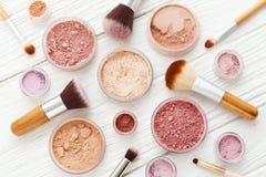Poudre et brosses de maquillage sur la configuration en bois blanche d'appartement photographie stock libre de droits