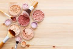 Poudre et brosses de maquillage sur le fond en bois images stock