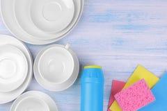 Poudre et gants de toilette de nettoyage avec les plats et les tasses blancs sur un b photographie stock