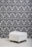 Pouf against wallpaper. White leather pouf against vintage style wallpaper in studio Stock Photo