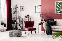 Pouf, armchair and sofa. Patterned pouf, red armchair and white sofa in living room interior with burgundy accents Stock Photography
