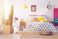 Pouf in folk bedroom interior. Pouf on brown carpet in bedroom interior with yellow lamp, round mirror and cactus. Folk bedroom concept Royalty Free Stock Photos