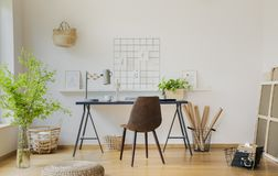 Pouf and plants in white home office interior with brown chair at desk with lamp. Real photo royalty free stock photo