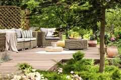 Garden furniture on wooden patio. Pouf on white round rug near garden furniture with blanket and pillows on wooden patio stock photo