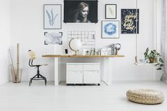 Pouf in white workspace interior. Pouf next to a wooden table and white cabinets in workspace interior with chair and plant on a swing Stock Images