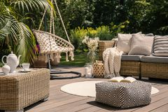 Pouf on wooden terrace with rattan sofa and table in the garden with hanging chair. Real photo. Concept stock images