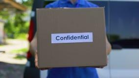 Poufny drobnicowy kurier w jednolitym mienie kartonie, dokument wysyłka zbiory wideo