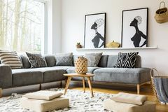 Poufs on carpet in bright african living room interior with grey. Corner sofa and posters. Real photo stock images