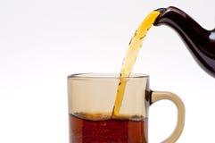 Pouirung de thé d'une théière dans la cuvette en verre Image libre de droits