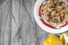 Poulet appétissant en sauce aigre-doux et riz avec les légumes et le poivre sur un concept noir et blanc de fond de plat blanc images libres de droits