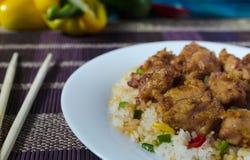 Poulet appétissant en sauce aigre-doux et riz avec les légumes et le poivre sur un dessus en gros plan de plat blanc du côté vue photo libre de droits