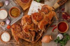 Poulet cuit au four par trois sur un fond en bois avec des sauces de différents types Les riches ont étendu la vue supérieure de  images stock