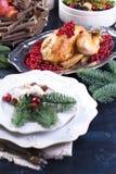 Poulet cuit au four sur un plateau avec les baies rouges sur une table en bois bleue avec une cuvette, plats servants image stock