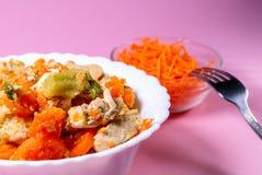 Poulet cuit, avec des légumes, carottes, chou d'un plat à côté des carottes fraîches de grille Fond rose Images stock