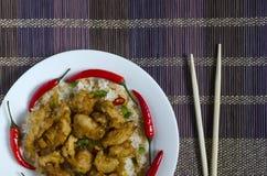 Poulet en sauce aigre-doux et riz avec des légumes d'un plat blanc sur l'espace coloré de copie de fond images stock