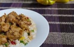 Poulet en sauce aigre-doux et riz avec des légumes d'un plat blanc sur l'espace coloré de copie de fond photo stock