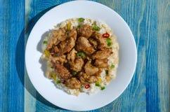 Poulet en sauce aigre-doux et riz avec des légumes sur le fond bleu de plat blanc photo libre de droits