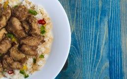 Poulet en sauce aigre-doux et riz avec les légumes et le poivre sur un endroit en bois bleu de fond de plat blanc sous l'advertis photos libres de droits