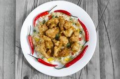 Poulet en sauce aigre-doux et riz avec les légumes et le poivre sur un fond noir et blanc de plat blanc photo libre de droits