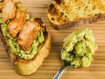 Poulet et avocat découpés en tranches sur le pain de maïs grillé Photographie stock