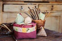 Poulet fait main et oeufs de tissu pour Pâques dans le sac piqué dans la maison de campagne Photographie stock libre de droits