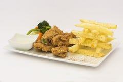 Poulet frit (chicharrà ³ n de pollo), pépites de poulet frit, pommes frites et légumes avec de la sauce chili Images stock